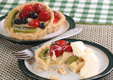 tartlet: mixed fruit tartlet on a white plate with fresh dairy cream
