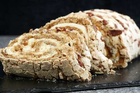 roulade: meringue roulade with fresh cream toffee and pecan nuts Stock Photo