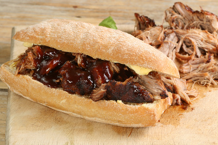 pulled pork with barbecue sauce on a crusty bread roll