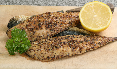 peppered: peppered mackerel fillets with lemon and parsley garnish Stock Photo