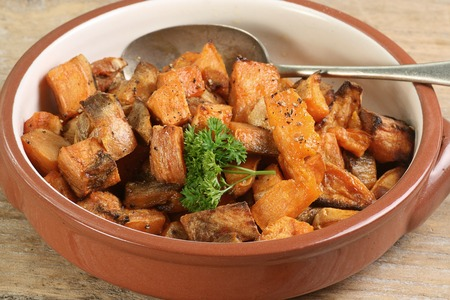 cubed: diced and roasted sweet potato with parsley garnish Stock Photo