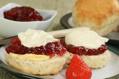 two halved devonshire scones with jam and fresh cream Foto de archivo