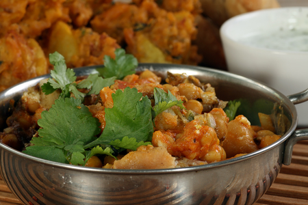 chaat: Indian food appetiser samosa chaat with pakora and mint yoghurt