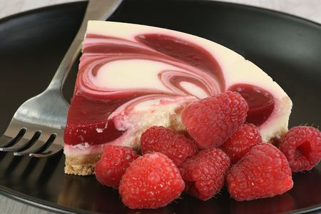 a portion: portion of raspberry ripple cheesecake with fresh raspberries Stock Photo