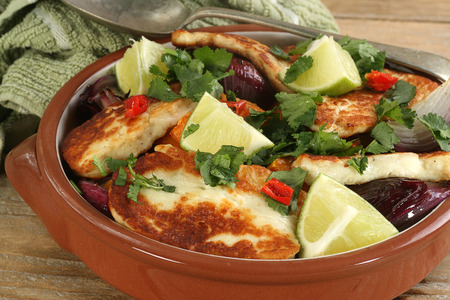 haloumi: grilled halloumi with red onion and sweet potato in a terracotta bowl Stock Photo