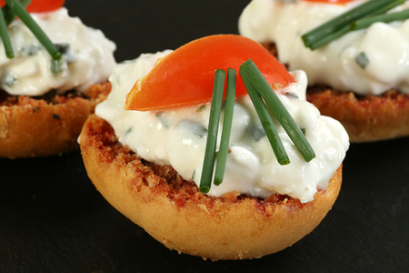 toasted buschetta slices with cottage cheese tomato and chives Stock Photo