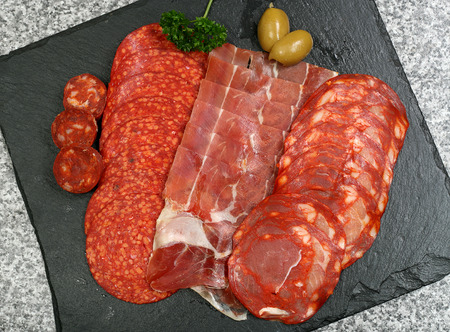 selection of sliced tapas meat on a slate background Stock Photo