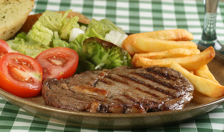juicy grilled ribeye beef steak with golden fries and salad Standard-Bild - 97510431