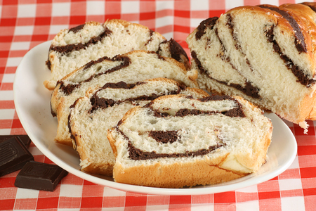 slices of chocolate filled briche on a red gingham cloth Standard-Bild - 97998598