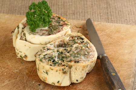 freshly prepared uncooked pork and apple roulade on a wooden board Standard-Bild