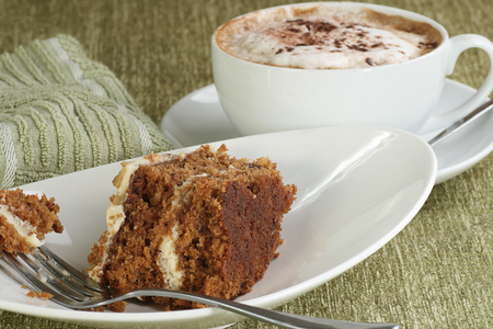 Slice of home baked delicious carrot cake with a cup of coffee Standard-Bild