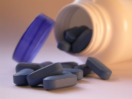 a prescription bottle spilling out blue pills