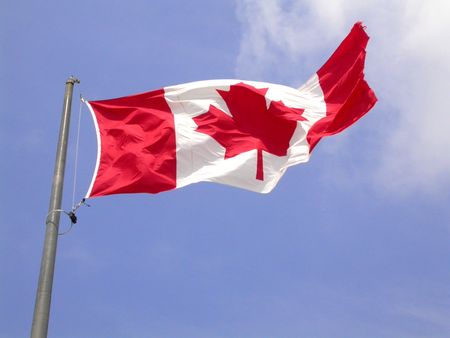 a canadian flag flapping in the wind from niagara falls