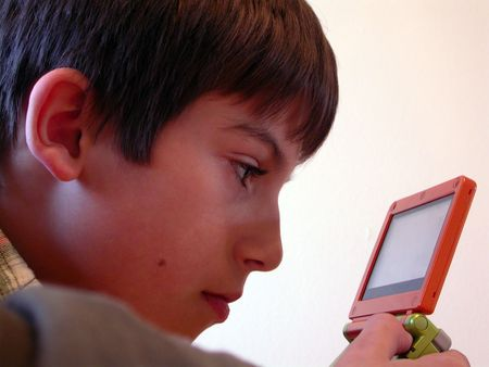 a young boy playing a handheld video game