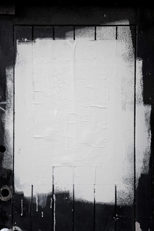 Rough white paint rolled over a black wooden textured background Stock Photo