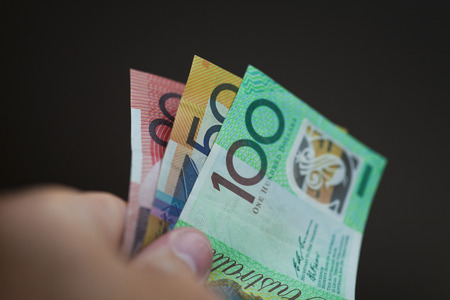 australian dollar notes: A hand holding a 20,50 and 100 Australian dollar notes on a black background