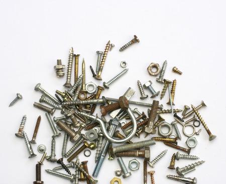 tuercas y tornillos: Una pila de tuercas, pernos, tornillos y otros sujetadores en un fondo blanco Foto de archivo