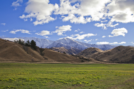 the south island: South Island mountain landscape scenery with a grass field in the foreground, Central Otago, New Zealand Stock Photo