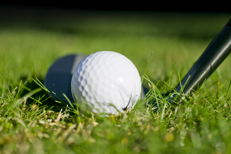 wedge: Lofted wedge resting behind a golf ball Stock Photo