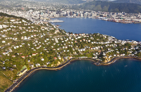 waterfront property: Houses in Wellington (Roseneath) with Wellington city in the background. Taken from a plane taking off from Wellington Airport.
