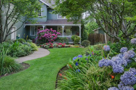 Entrance to a home through a beautiful garden, highlighted by rose and blue hydrangeas. Stock Photo