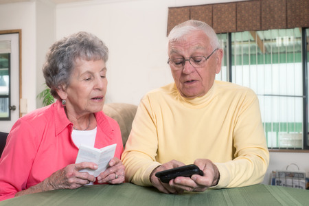 navigate: An elderly couple confer as they navigate the instructions for their new phone. Stock Photo