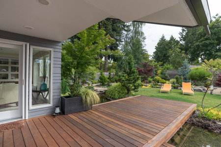 deck: A perspective view of a contemporary Pacific Northwest home with a deck bridging a pond that leads to a pair of modern yellow loungers in a landscaped yard.