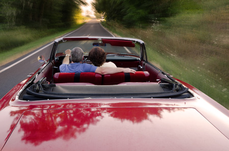 A middle-aged couple snuggle together as they zoom down a county road in a classic red convertable, perhaps on a Sunday drive as they enjoy the experience and each other 免版税图像