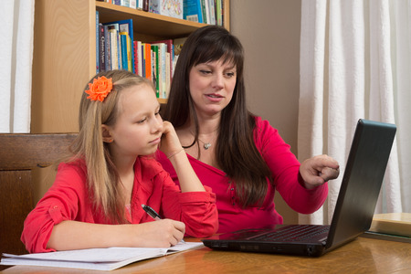A mother and her young daughter sit in front of a laptop as they research information for her homework.