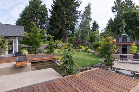 Back yard of a contemporary Pacific Northwest home featuring a deck a spanning creek-like water feature with a landscaped lawn and custom patio fireplace in the background. Stock Photo