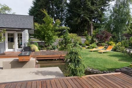 Achtertuin van een moderne Pacific Northwest huis met een dek verspreid over een kreek-achtige waterpartij met een gazon en twee gazon uitnodigende stoelen op de achtergrond.