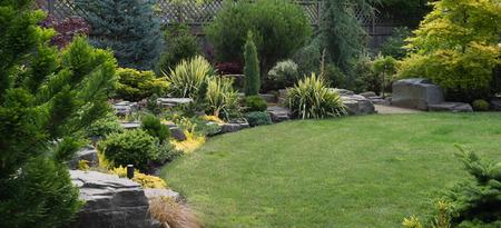 Uiteraard gebeeldhouwde platte top gesteenten uit ten noordwesten van Oregon worden in een fraai aangelegde achtertuin geplaatst onder een verscheidenheid aan vaste plant evergreens en struiken. Stockfoto