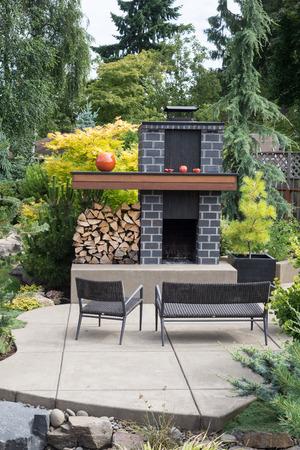 Een lange, speciaal ontworpen open haard met grijze bakstenen en veel brandhout zit op een uitnodigende terras in een Pacific Northwest achtertuin. Stockfoto