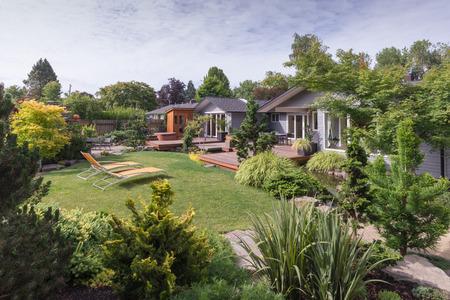 現代的な家は、岩と太平洋岸北西部の穏やかな夏の日のフォア グラウンドで常緑な造園裏庭の芝生を超えて見ることができます。
