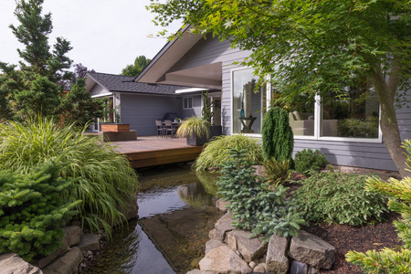 A water feature emulating a creek flows under a deck and between landscaped rocks with a contemporary home in the background.