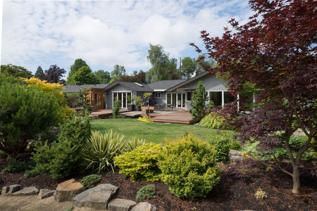 岩やエバー グリーン造園、フォア グラウンドで穏やかな夏の日に太平洋岸北西部である裏庭の芝生を越えて現代的な家を見てすることができます。 写真素材 - 36467439