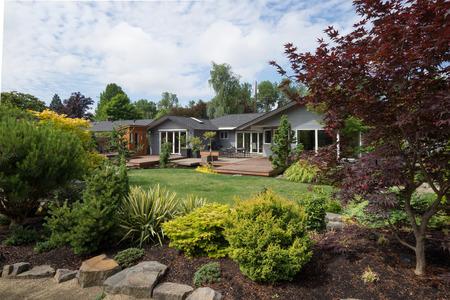 Een eigentijdse huis kan worden gezien buiten de achtertuin gazon met rock en groenblijvende landscaping op de voorgrond op een milde zomer dag in de Pacific Northwest. Stockfoto