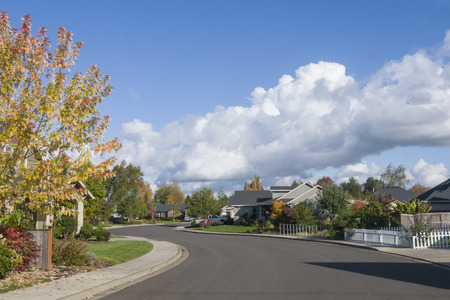 An empty street curves though a suburban neighborhood on a beautiful fall day under a bright blue sky with puffy white clouds. 写真素材