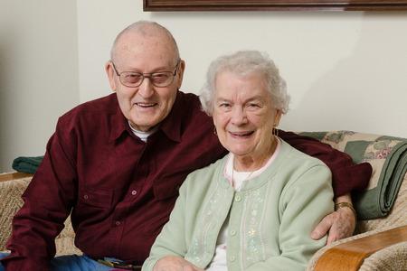 Casual close-up portret van een gelukkig paar ouderen in de tachtig, zittend op een sofa in de woonkamer.