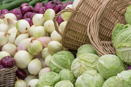 Two woven baskets highlight a river of organic onions and cabbages flowing towards the viewer at a farmers market.