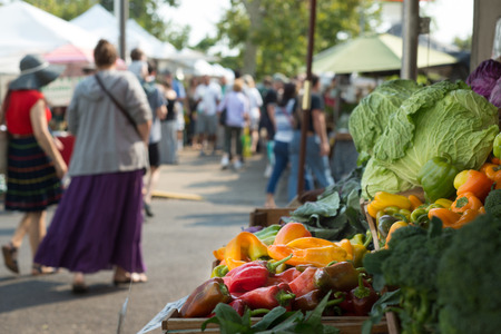 Colorful fresh produce are highlighted in the foreground with a busy farmers market filled with shoppers in the background.