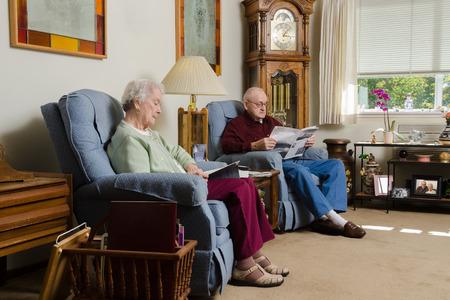 Een paar ouderen rustig te genieten van elkaars gezelschap als ze lezen samen in hun comfortabele woonkamer.
