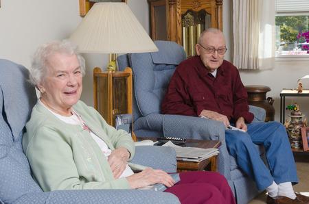 Een gelukkige bejaarde coouple verwelkomt de kijker naar hun huis. Stockfoto
