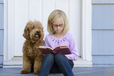 A serious young girl sits on the steps of her house reading a book with her dog next to her