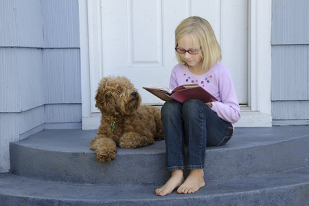 engrossed: A young girl sitting on the front steps is engrossed in a book as her dog sits beside her