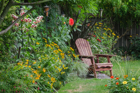landscaped garden: A weathered wood chair sits at the end of a stone walkway, hidden behind colorful zinnias.