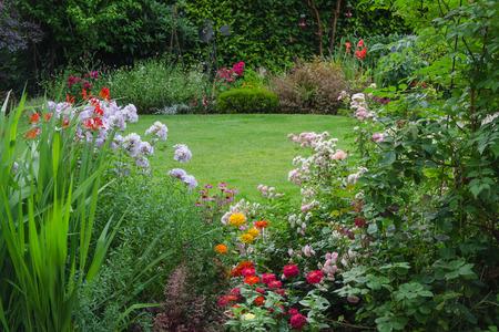 色とりどりの花に囲まれた緑豊かな裏庭の芝生の様子 写真素材