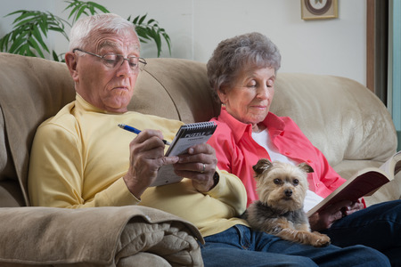 An older couple relaxes together with their lap dog keeping them company.