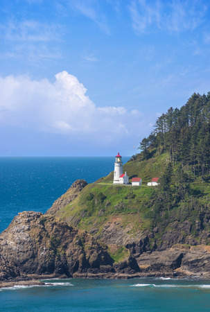 punctuate: Distant clouds punctuate a bright blue sky at the Heceta Head lighthouse on Oregon
