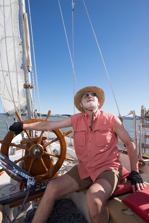 A senior man at the helm of his classic sailboat judges the wind in his sails under a bright blue sky.